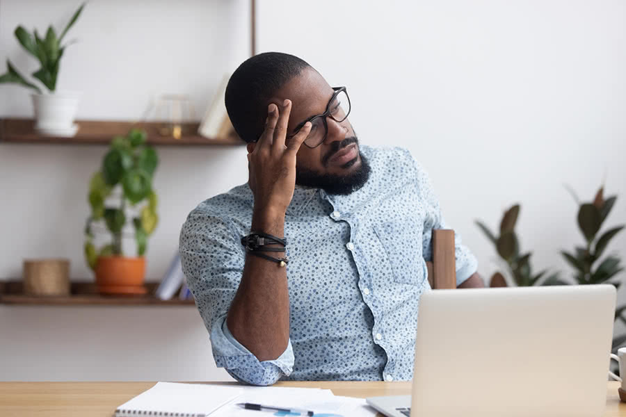 young man frustrated about finances and holding his head
