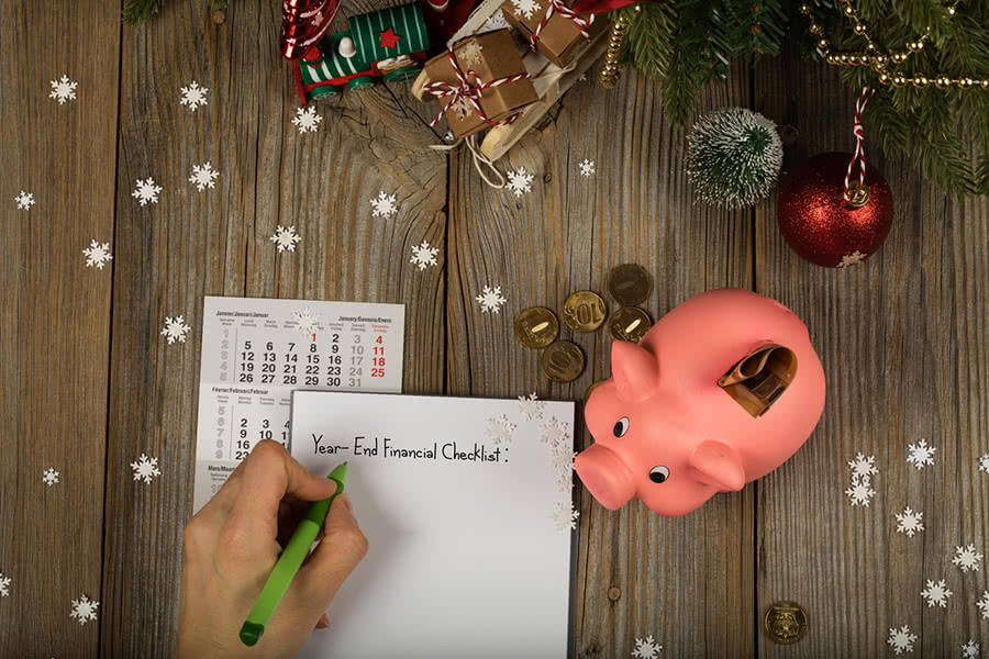 Sheet of paper and year-end financial checklist and piggy bank to save money for the holidays