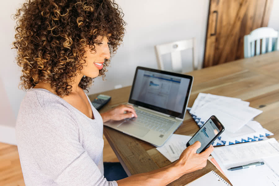 woman doing finances for side hustle with smartphone and computer at home