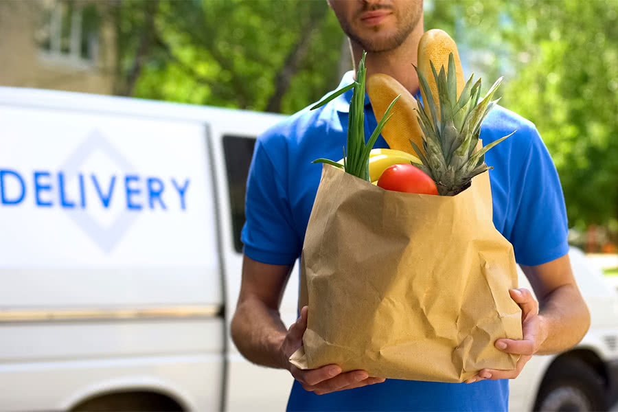 man holding bag of fresh groceries in front of delivery truck